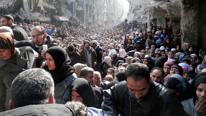 Residents wait to receive food aid distributed by the U.N. Relief and Works Agency (UNRWA) at the besieged al-Yarmouk camp, south of Damascus on January 31, 2014, in this handout picture made available to Reuters February 26, 2014..(Reuters / UNRWA)