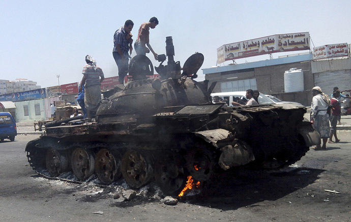 People stand on a tank that was burnt during clashes on a street in Yemen's southern port city of Aden March 29, 2015. (Reuters/Stringer)