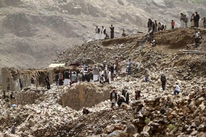 People stand on the rubble of houses destroyed by an air strike in Okash village near Sanaa April 4, 2015. (Reuters / Mohamed al-Sayaghi)