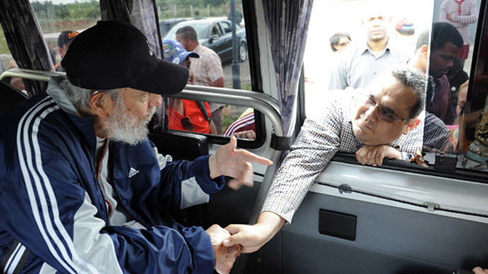 """Former Cuban president Fidel Castro (L) greeting a member of the Venezuelan delegation """"II flight Solidarity Bolivar-Marti"""" who are in Cuba taking part in social and political activities, in Havana on March 30, 2015. (AFP Photo / www.cubadebate.cu)"""