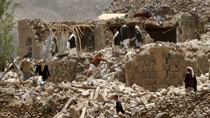 People stand on the rubble of houses destroyed by an air strike in Okash village near Sanaa April 4, 2015. (Reuters/Mohamed al-Sayaghi)