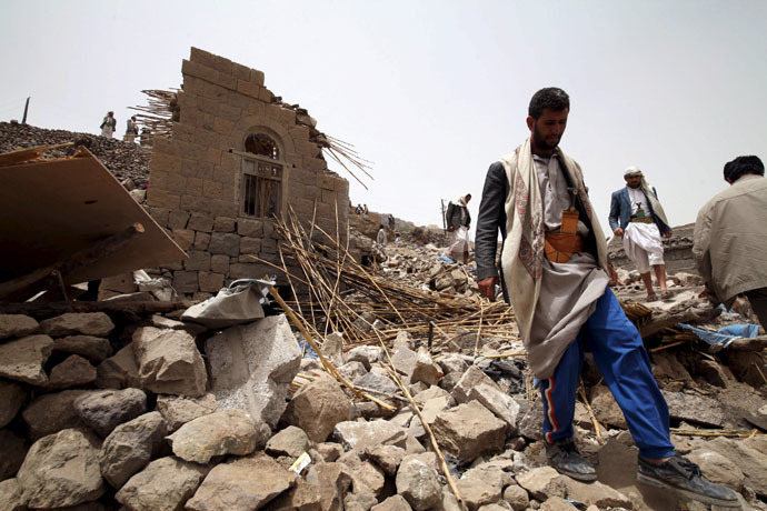 People stand on the rubble of houses destroyed by an air strike in the Okash village near Sanaa April 4, 2015. (Reuters/Mohamed al-Sayaghi)