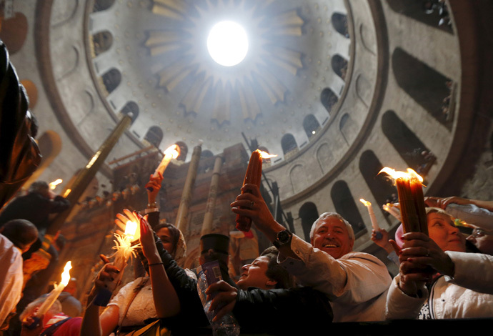 Worshippers hold candles as they take part in the Christian Orthodox Holy Fire ceremony at the Church of the Holy Sepulchre in Jerusalem's Old City, April 11, 2015. (Reuters/Ammar Awad)