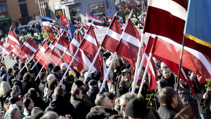 People hold flags as they participate in the annual procession commemorating the Latvian Waffen-SS (Schutzstaffel) unit, also known as the Legionnaires, in Riga March 16, 2015. (Reuters/Ints Kalnins)