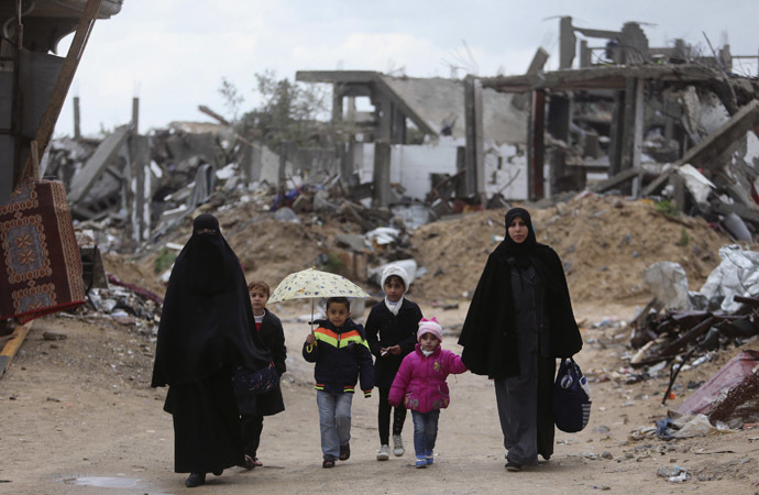 Palestinians walk near the ruins of houses that witnesses said were destroyed or damaged by Israeli shelling during a 50-day war last summer, on a winter day east of Gaza City February 20, 2015. (Reuters/Ibraheem Abu Mustafa)