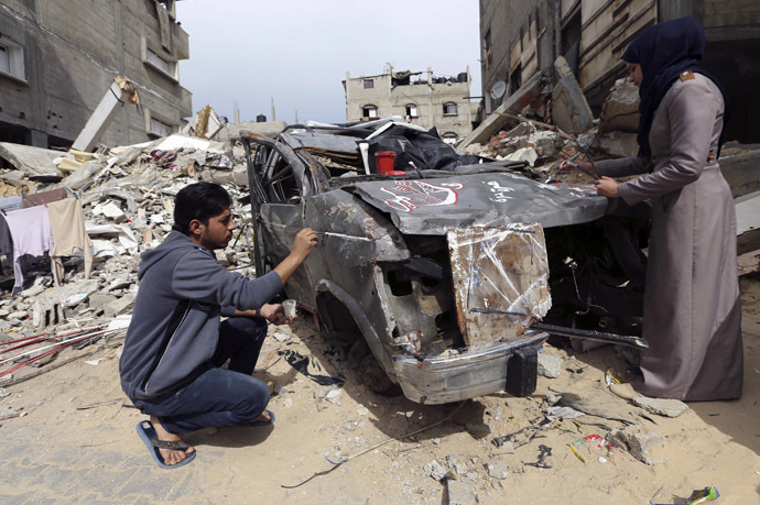 Palestinian artists paint on the remains of car that witnesses said was destroyed by Israeli shelling during a 50-day war last summer, in Rafah in the southern Gaza Strip February 24, 2015. (Reuters/Ibraheem Abu Mustafa)