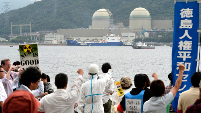 Protesters raise their fists at a freighter (C), carrying plutonium-uranium mixed oxide (MOX) fuel processed in France, as it arrives at Kansai Electric Power Co.'s Takahama nuclear power plant in Takahama town, Fukui prefecture, in this photo taken by Kyodo June 27, 2013.(Reuters / Kyodo)