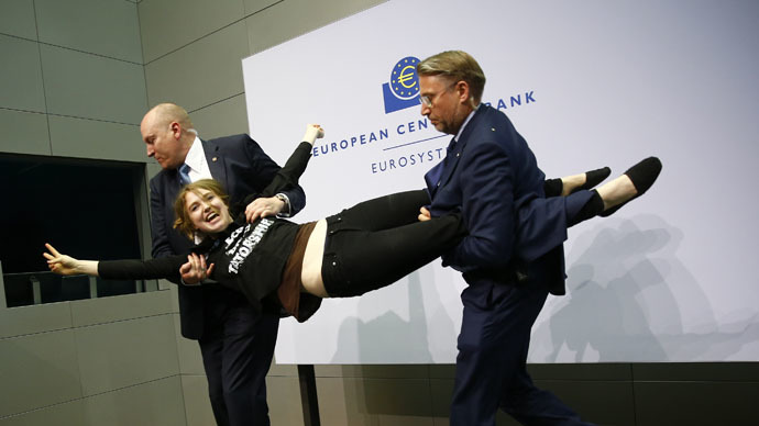 Security officers detain a protester who jumped on the table in front of the European Central Bank President Mario Draghi during a news conference in Frankfurt, April 15, 2015. (Reuters/Kai Pfaffenbach)