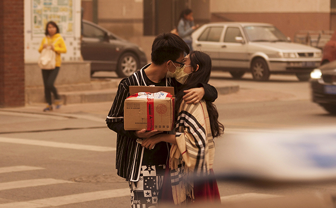 A couple wearing masks kiss along a street during a sandstorm in Beijing, April 15, 2015 (Reuters / China Daily)