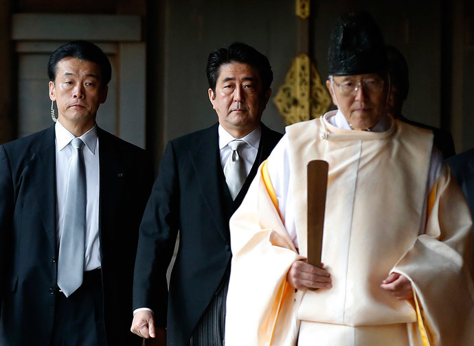 Japan's Prime Minister Shinzo Abe (C) is led by a Shinto priest as he visits Yasukuni shrine in Tokyo December 26, 2013. (Reuters / Toru Hanai)