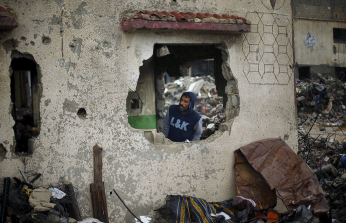 A Palestinian man takes cover inside the remains of a house that witnesses said was destroyed by Israeli shelling during a 50-day war in 2014 summer, on a rainy day in Beit Hanoun town in the northern Gaza Strip April 12, 2015. (Reuters/Suhaib Salem)