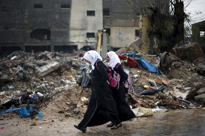 Palestinian schoolgirl walk past the rubble of a house that witnesses said was destroyed by Israeli shelling during a 50-day war in 2014 summer, on a rainy day in Beit Hanoun town in the northern Gaza Strip April 12, 2015. (Reuters/Suhaib Salem)