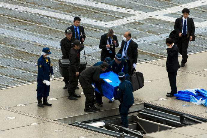Officials carry a blue box that local media reported contains a drone from the rooftop of Prime Minister Shinzo Abe's official residence in Tokyo April 22, 2015. (Reuters / Toru Hanai)