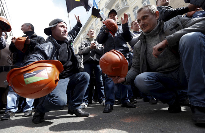 Miners bang their helmets on the ground during a rally to demand the payment of their salaries from the government in central Kiev April 22, 2015. (Reuters / Valentyn Ogirenko)