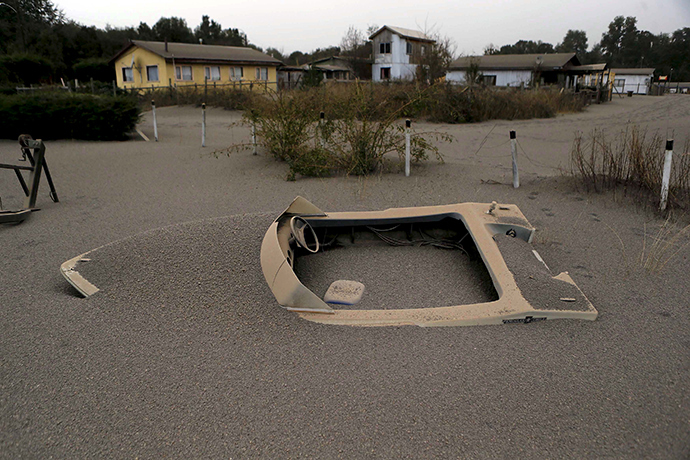 A boat is seen in a house backyard at Ensenada town which is covered with ash from Calbuco volcano near Puerto Varas city, April 23, 2015 (Reuters / Ivan Alvarado)