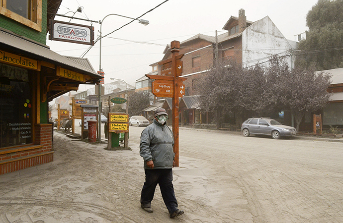 A man wearing a surgical mask to protect himself against ash from Calbuco volcano, walks by the Patagonian Argentine area of San Marin de Los Andes April 23, 2015 (Reuters / Patricio Rodriguez)