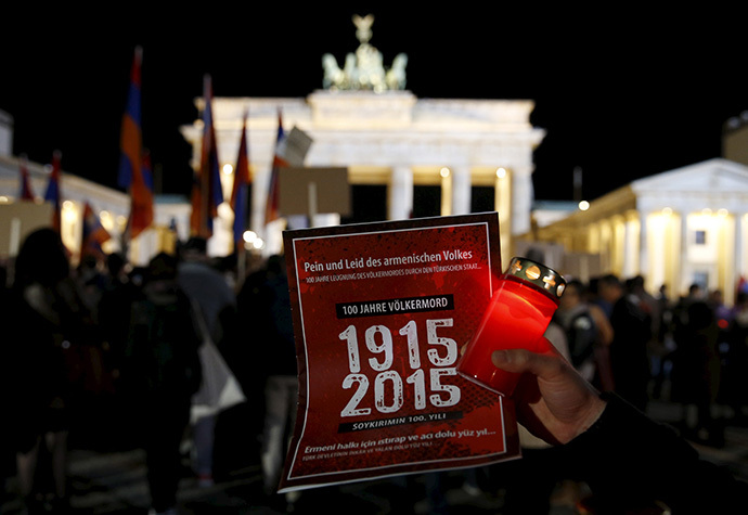 A participant holds a candle and a sign during a memorial march by armenians in front of the Brandenburg Gate after an Ecumenical service marking the 100th anniversary of the mass killings of 1.5 million Armenians by Ottoman Turkish forces, at the cathedral in Berlin April 23, 2015. (Reuters/Fabrizio Bensch)