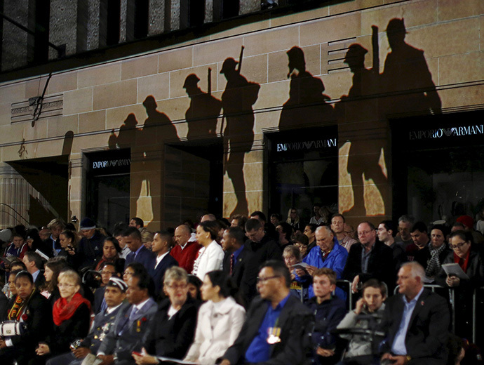 Silhouettes of ANZAC (Australian and New Zealand Army Corps) troops are projected onto the wall of a building above the crowd during the dawn of ANZAC Day 100th anniversary commemoration at Sydney's Cenotaph in Australia, April 25, 2015. (Reuters/Jason Reed)