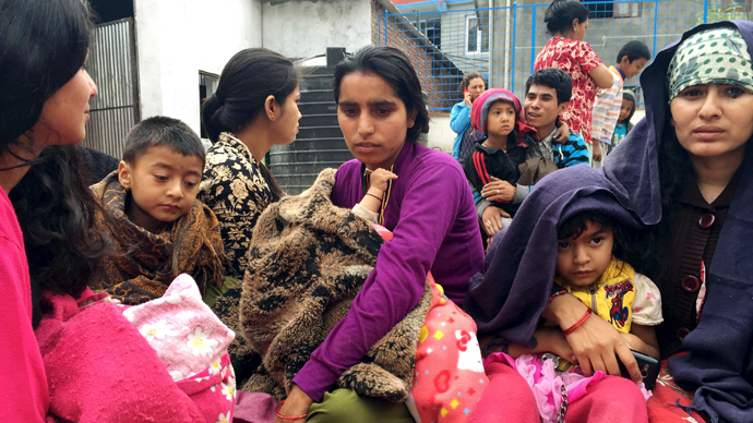 People wait at a school after a 7.7 magnitude earthquake struck, in Kathmandu, Nepal, April 25, 2015. (Reuters)
