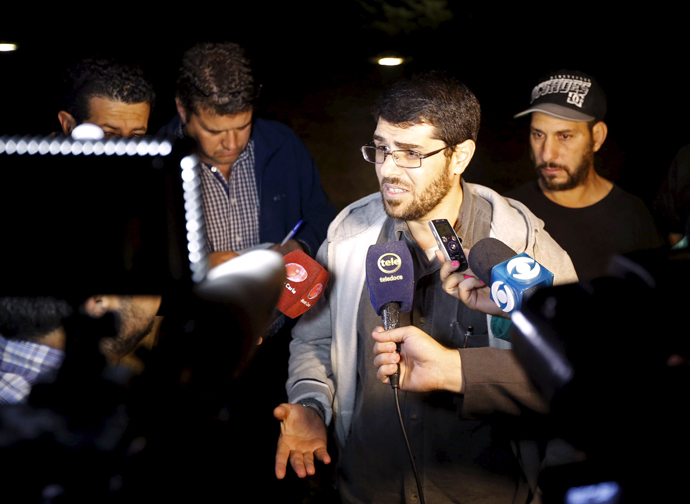Former Guantanamo detainees Omar Mahmoud Faraj (2nd R) and Abdul din Muhammed Tawes (R) talk to the media in front of the U.S. embassy in Montevideo, April 24, 2015. (Reuters / Andres Stapff)