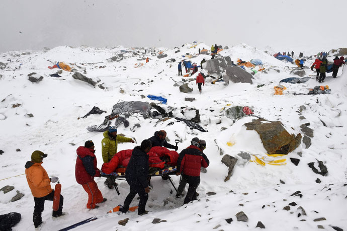 In this photograph taken on April 25, 2015, rescuers use a makeshift stretcher to carry an injured person after an avalanche triggered by an earthquake flattened parts of Everest Base Camp. (AFP Photo/Roberto Schmidt)