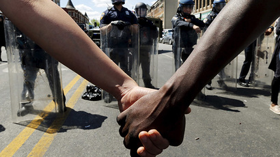 Members of the community hold hands in front of police officers in riot gear outside a recently looted and burned CVS store in Baltimore, Maryland, United States April 28, 2015. (Reuters/Jim Bourg)