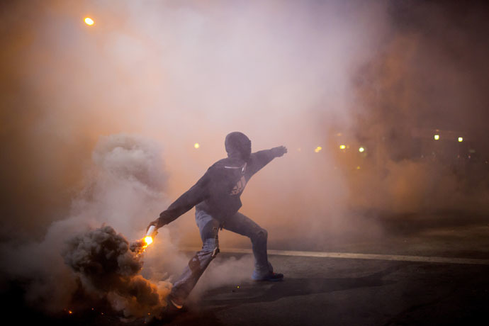 A protester throws a gas canister back at police during clashes at North Ave and Pennsylvania Ave in Baltimore, Maryland April 28, 2015. (Reuters/Eric Thayer)