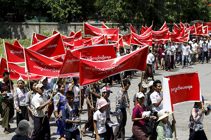 Workers carry banners with messages in support of workers' rights during a march to mark Labour Day in Yangon May 1, 2015 (Reuters / Soe Zeya Tun)