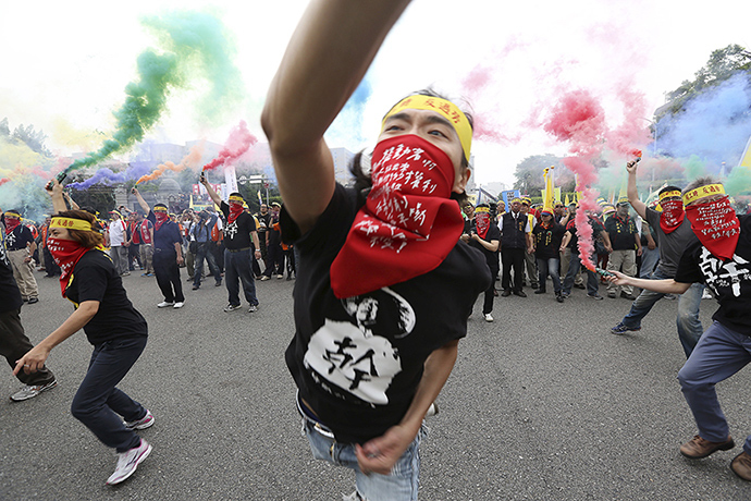 People throw smoke grenades during the annual Labour Day protest in front of Presidential Office in Taipei, Taiwan, May 1, 2015 (Reuters / Patrick Lin)