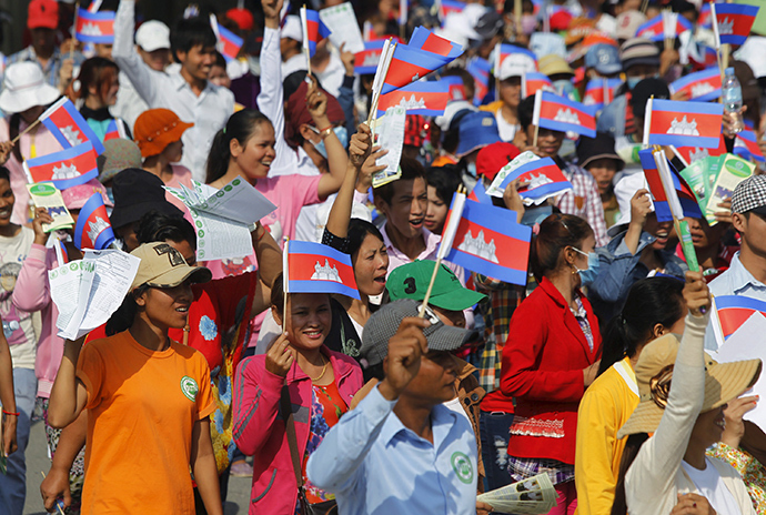 Garment workers shout and wave Cambodian national flags as they take part in a protest calling on the government to raise wages during a march to mark Labour Day in Phnom Penh May 1, 2015 (Reuters / Samrang Pring)