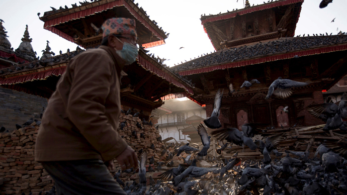 A man arrives to feed pigeons at a temple damaged after an earthquake in Kathmandu, Nepal, May 3, 2015. (Reuters / Danish Siddiqui)