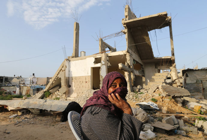 A Palestinian woman sits near her house, that witnesses said was destroyed by Israeli shelling during a 50-day war last summer, in Khan Younis in the southern Gaza Strip, March 10, 2015. (Reuters/Ibraheem Abu Mustafa)