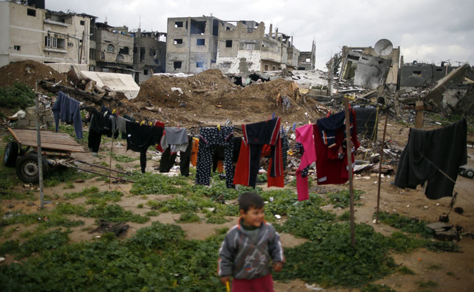 A Palestinian boy plays near the ruins of his family house that witnesses said was destroyed by Israeli shelling during a 50-day war last summer, east of Gaza City February 18, 2015. (Reuters/Mohammed Salem)