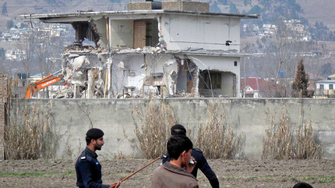 Policemen and residents stand near while demolition work is carried out on the building where al Qaeda leader Osama bin Laden was killed by US special forces in Abbottabad (Reuters / Sultan Dogar)