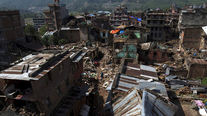 Local residents walk past collapsed houses after the April 25 earthquake in Sankhu on the outskirts of Kathmandu, Nepal, May 11, 2015. (Reuters/Athit Perawongmetha)