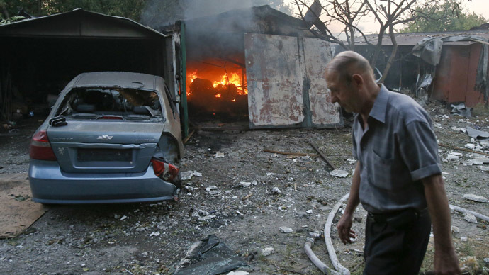 ARCIVE PHOTO: A man walks past a garage set ablaze by what locals say was shelling by Ukrainian forces in Donetsk, September 4, 2014 (Reuters / Maxim Shemetov)