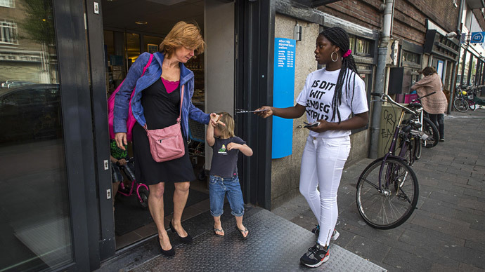 "A woman wearing a T-shirt reading ""Is this white enough for you? "" gives out a leaflet on May 22, 2015, in Amsterdam. (AFP Photo / Remko DE Waal)"