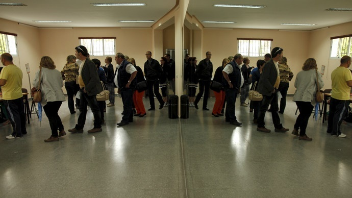 People are reflected in a mirror (R) as they wait in line to cast their ballots at a polling station during municipal elections in Ronda, southern Spain May 24, 2015.(Reuters / Jon Nazca)