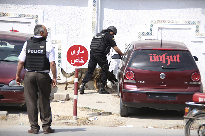 A Tunisian anti-terrorism brigade officer lead his dog outside the Bouchoucha military base after a shooting in Tunis, Tunisia May 25, 2015 (Reuters / Zoubeir Souissi)