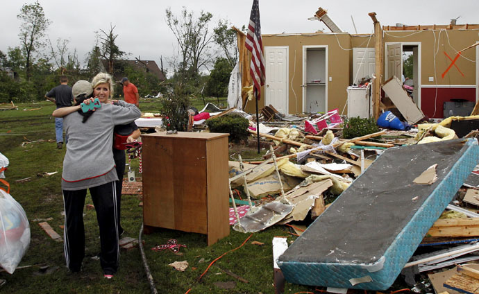 Amy Parrish (2nd L) hugs a woman as she gathers personal items from her home after a tornado swept through the area the previous night in Van, Texas May 11, 2015. (Reuters/Mike Stone)