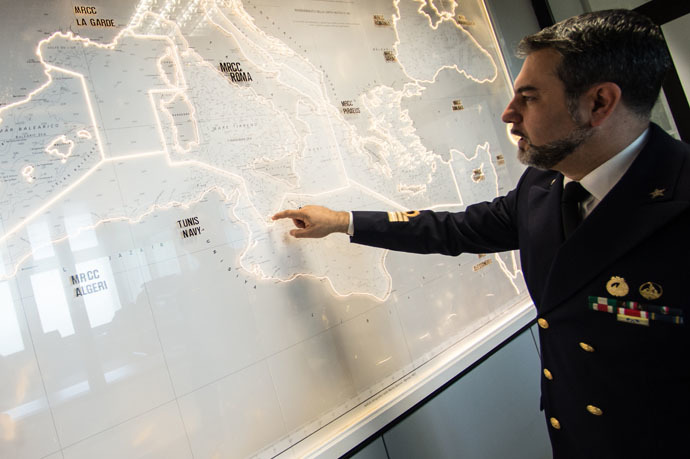 Italian officer Gianluca D'Agostino of the Italian Coast Guard, looks at a map of the Mediterranean Sea, in the control center at the headquarter of Italian Coast Guard, on May 28 2015, in Rome. (AFP Photo/Andreas Solaro)