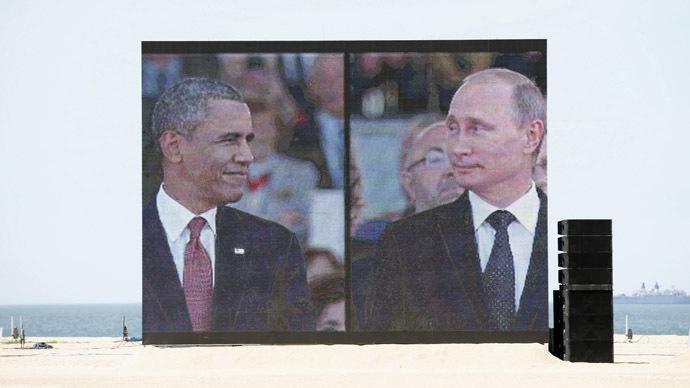 A huge video screen on Sword Beach shows U.S. President Barack Obama and Russian President Vladimir Putin. (Reuters/Kevin Lamarque)
