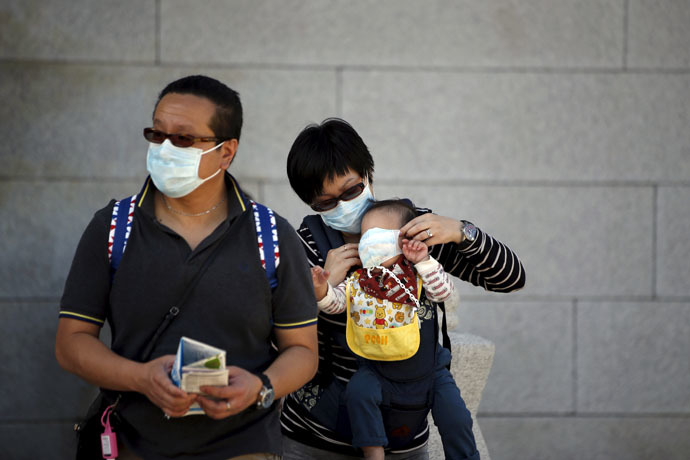 A Chinese tourist puts a mask on her child's face to prevent contracting Middle East Respiratory Syndrome (MERS) at the Gyeongbok Palace in central Seoul, South Korea June 3, 2015. (Reuters/Kim Hong-Ji)