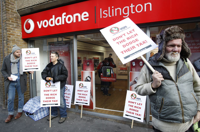 Demonstrators stand poutside a branch of Vodafone as they protest against the company not paying enough tax, in north London, December 11, 2010. (Reuters/Andrew Winning)