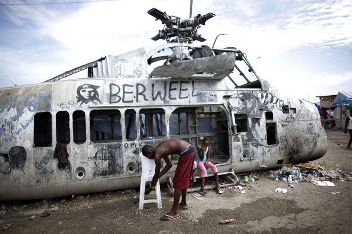 An earthquake survivor washes his hands in a bucket, donated by Haiti's Red Cross to control infections, near a damaged helicopter in a provisional camp in downtown Port-au-Prince October 30, 2010. (Reuters/Eduardo Munoz)