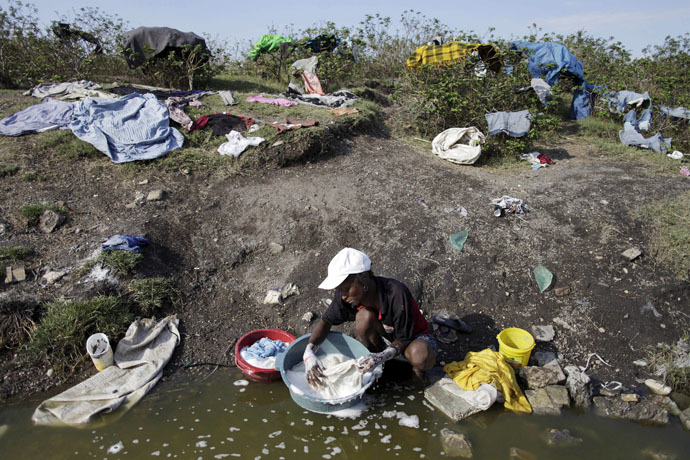 A woman washes her clothes in a pond close to Cite Soleil, in Port-au-Prince, March 21, 2015. (Reuters/Andres Martinez Casares)