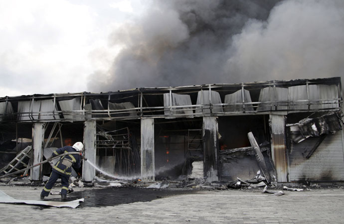 A firefighter works to extinguish a fire at a local market, which was recently damaged by shelling, in Donetsk, Ukraine, June 3, 2015. (Reuters/Alexander Ermochenko)