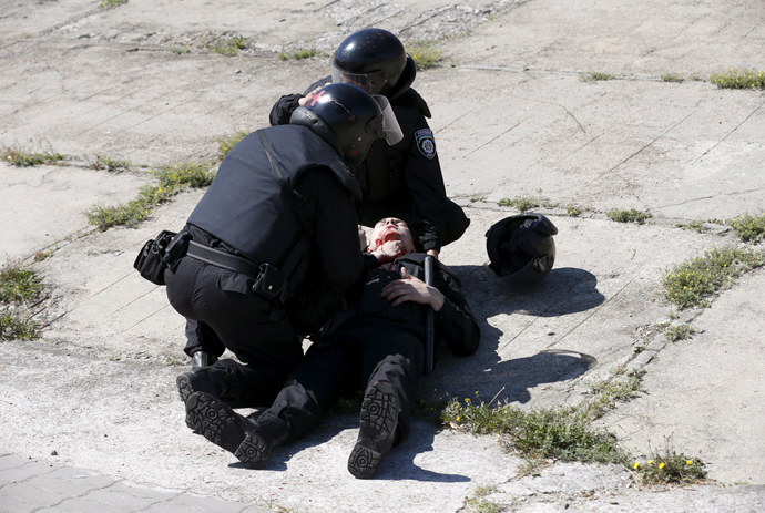 Interior Ministry members apply first aid to their colleague who was injured in clashes with anti-gay protesters during the so-called Equality March, organized by a lesbian, gay, bisexual and transgender (LGBT) community, in Kiev, Ukraine, June 6, 2015. (Reuters / Stringer)