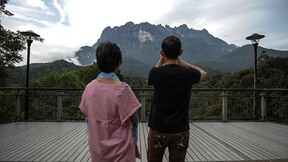 A tourist (R) takes pictures of Malaysia's Mount Kinabalu a day after the earthquake in Kundasang, a town in the district of Ranau on June 6, 2015. (AFP Photo/Mohd Rasfan)