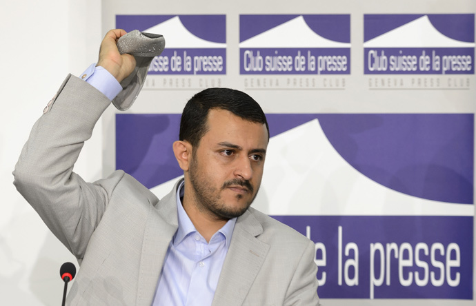 Head of Yemeni rebel's delegation Hamza al-Houthi throws back a shoe thrown at him by a representative of South Yemen during clashes at a press conference at the Geneva Press Club on June 18, 2015 in Geneva on Yemen peace talks. (AFP Photo / Fabrice Coffrini)
